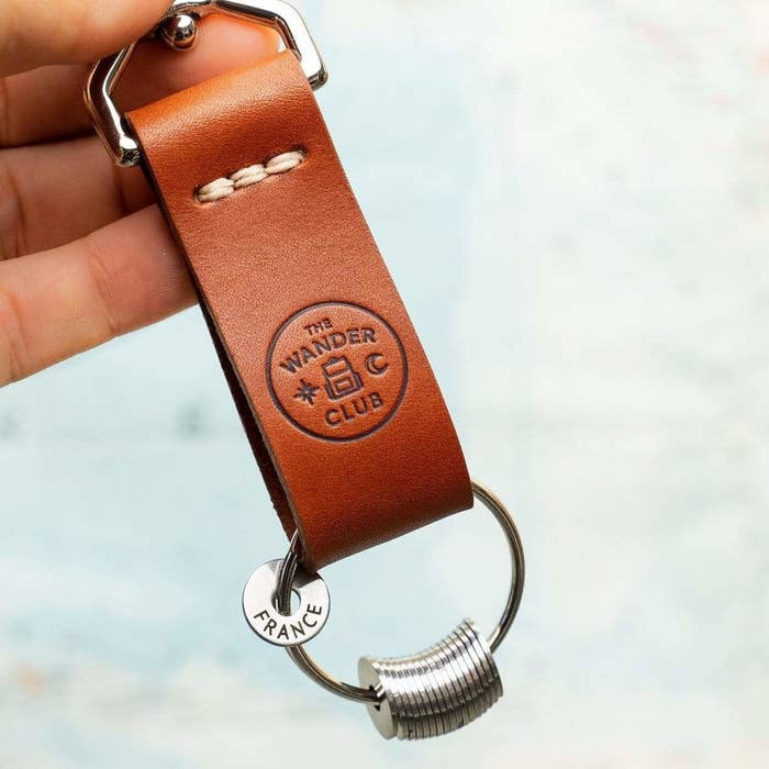 A brown keychain with a keyring holding several engraved tokens; one is engraved to say France