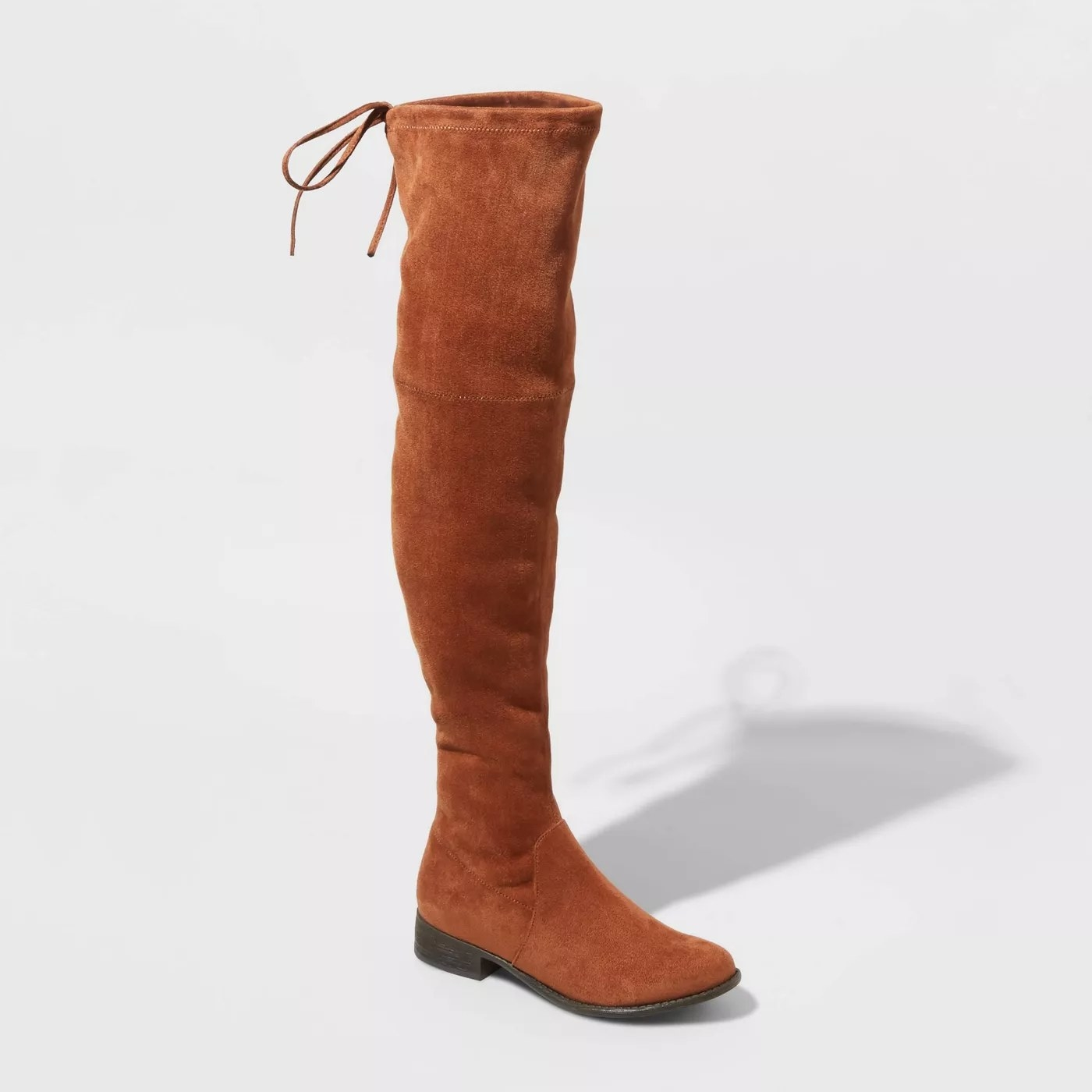 Dark camel colored knee high boots with black sole.