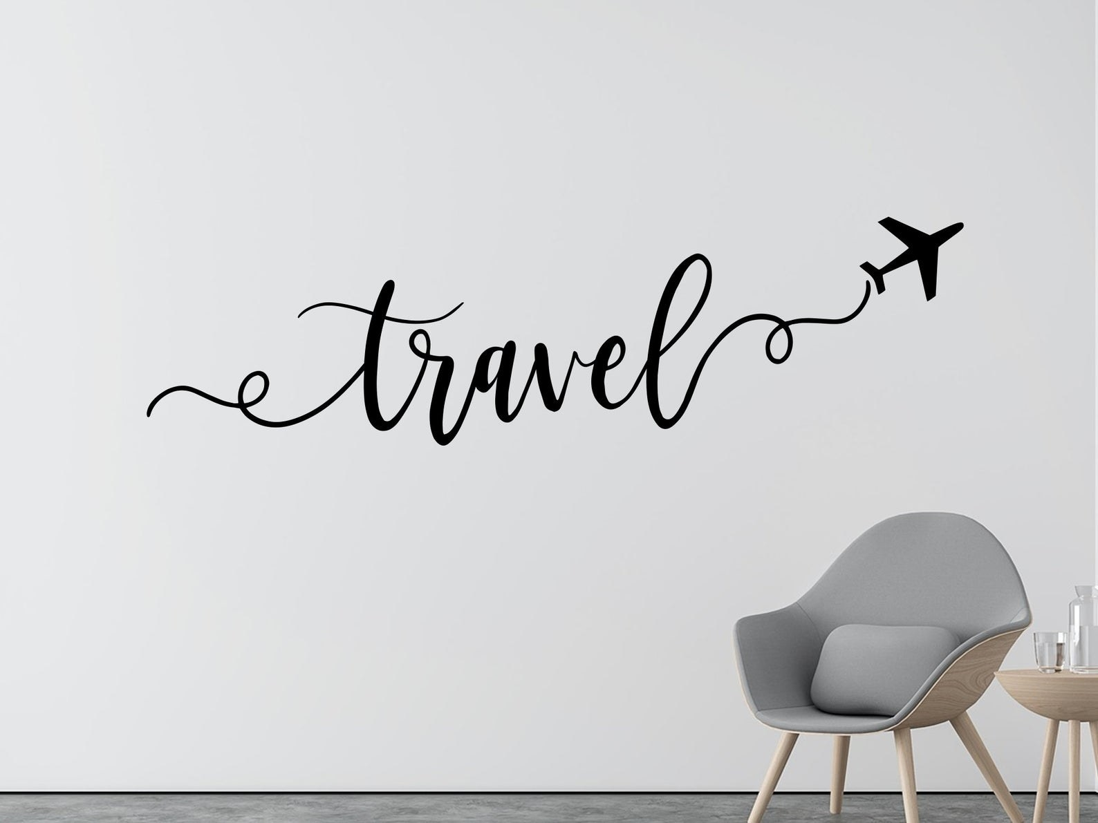 "A wall decal in script that says ""travel"" and has a plane silhouette"