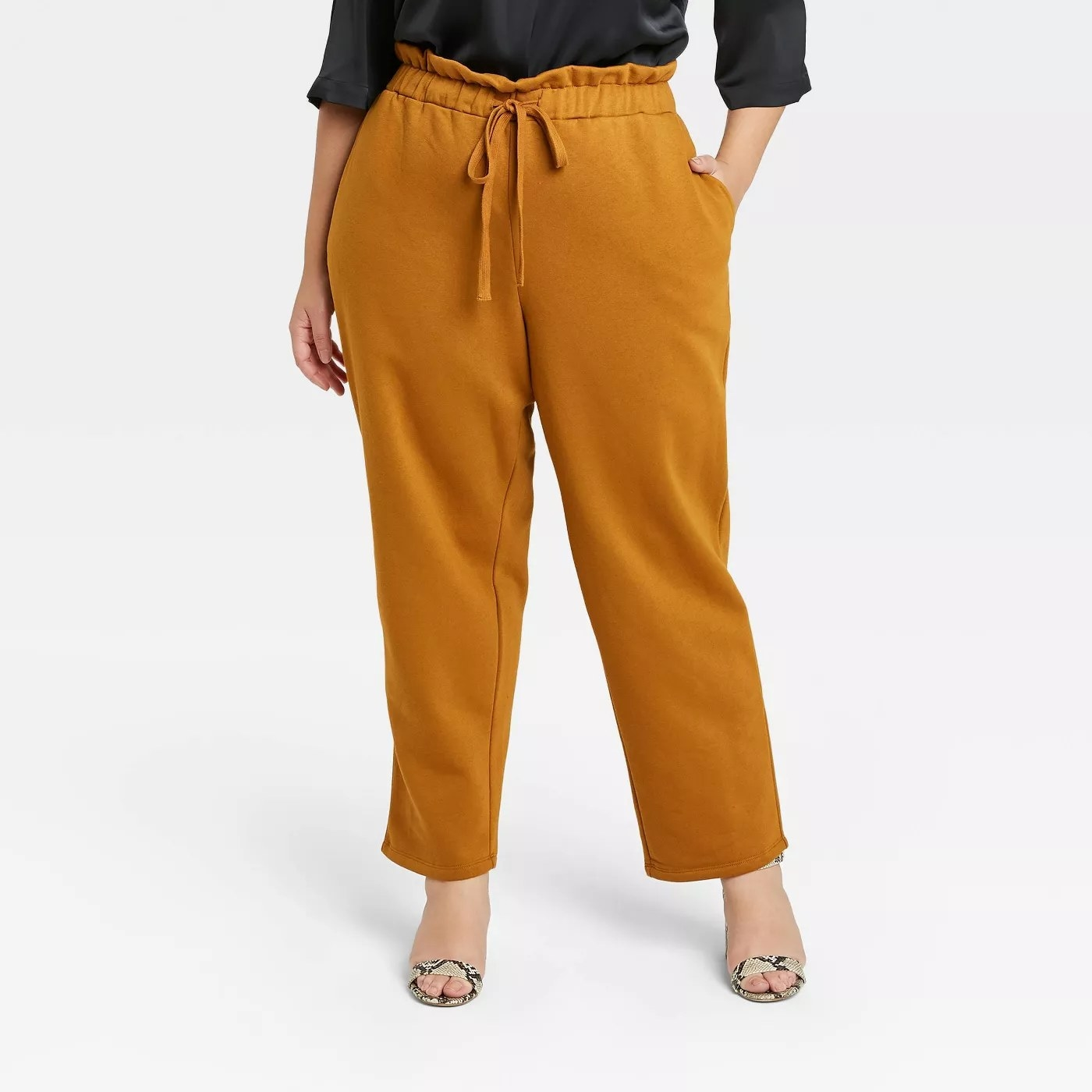 Mustard colored jogger pants paired with open toe python heels