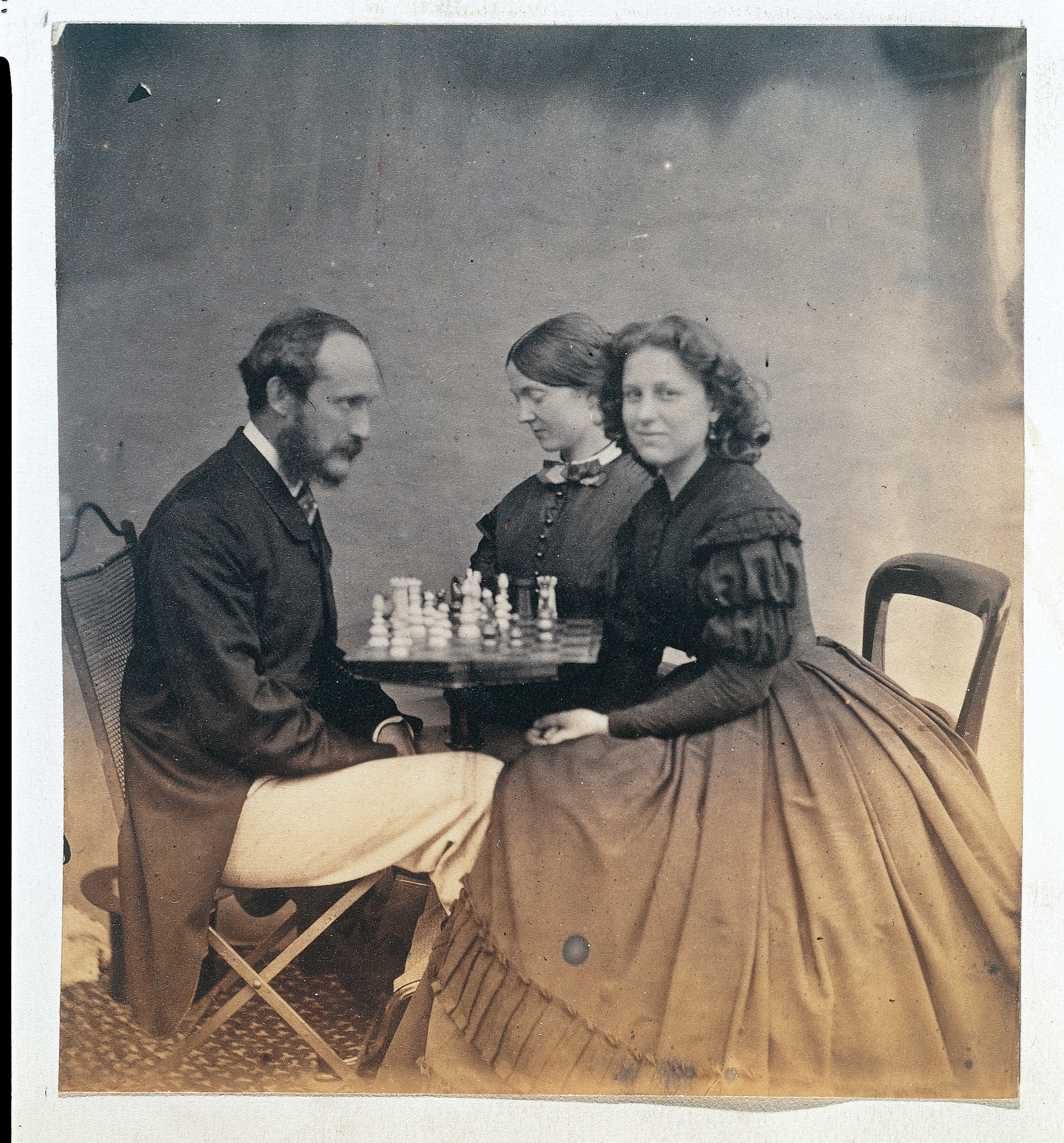 An old photograph of two women sitting across a table and playing chess with a man