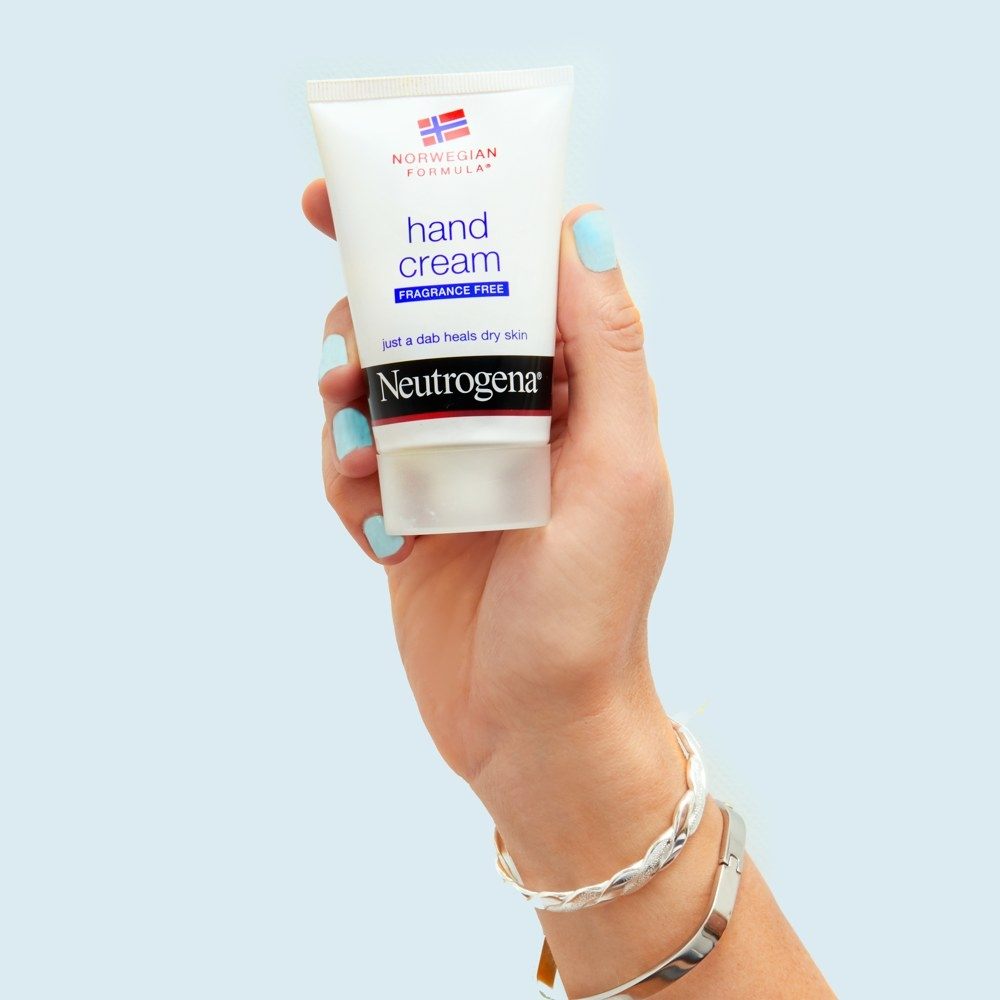 a hand holding a white squeeze bottle of hand cream