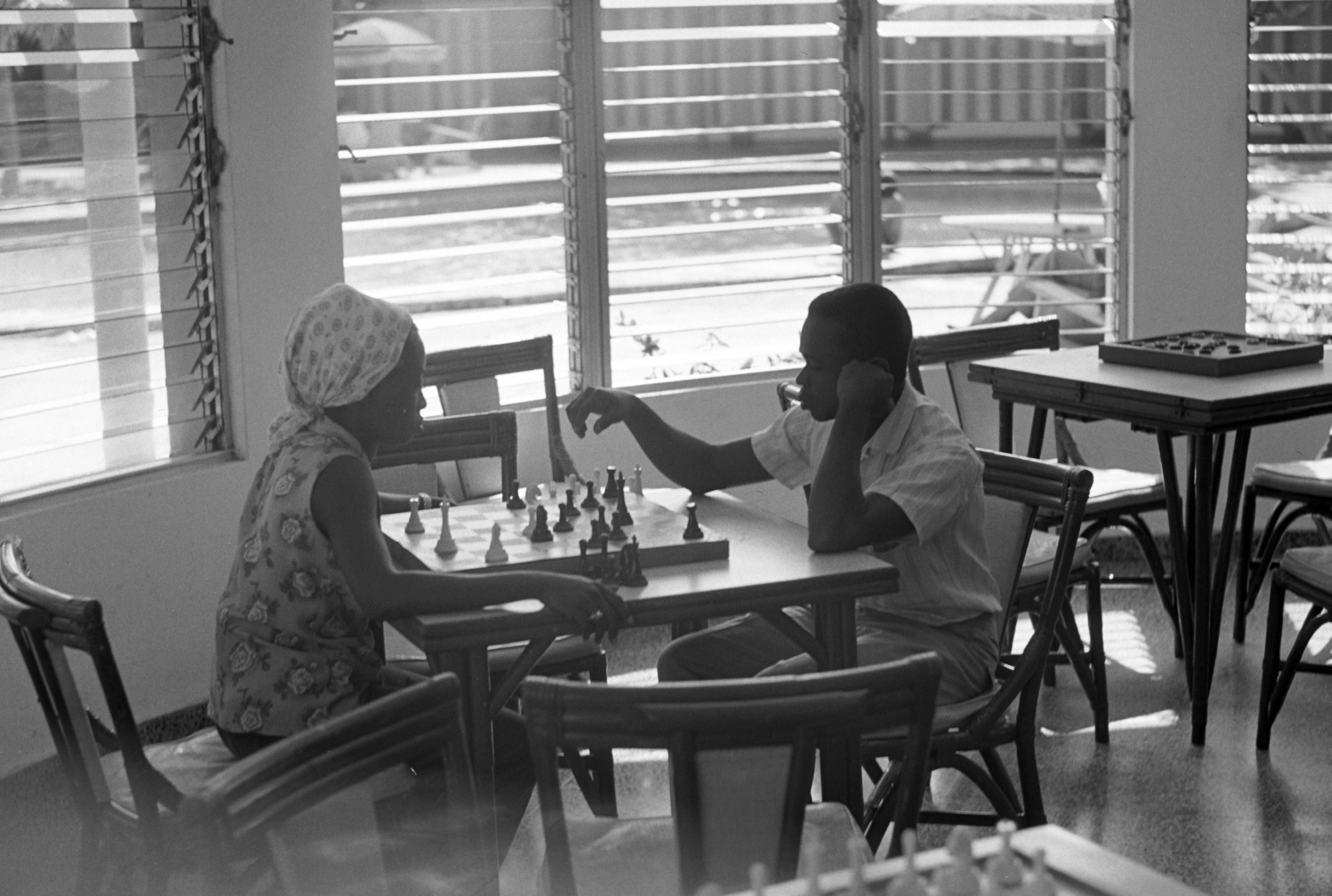 A man and woman play chess in a hotel lobby