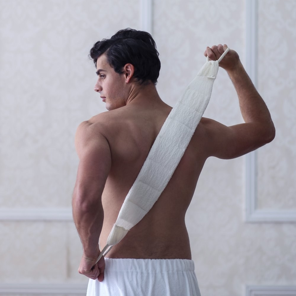 a person using a white cloth back scrubber with two handles on their back
