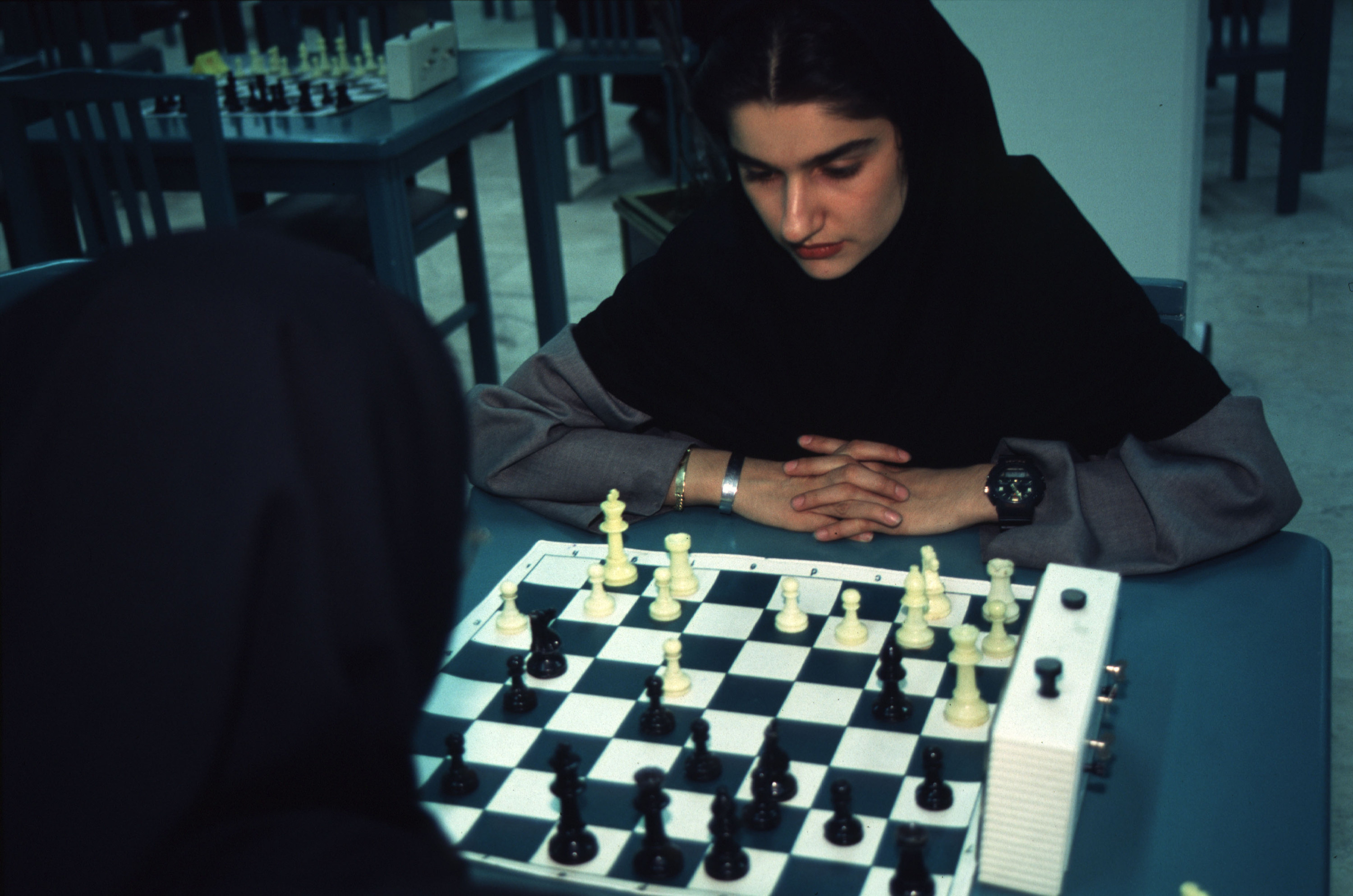 Two women with head coverings playing chess