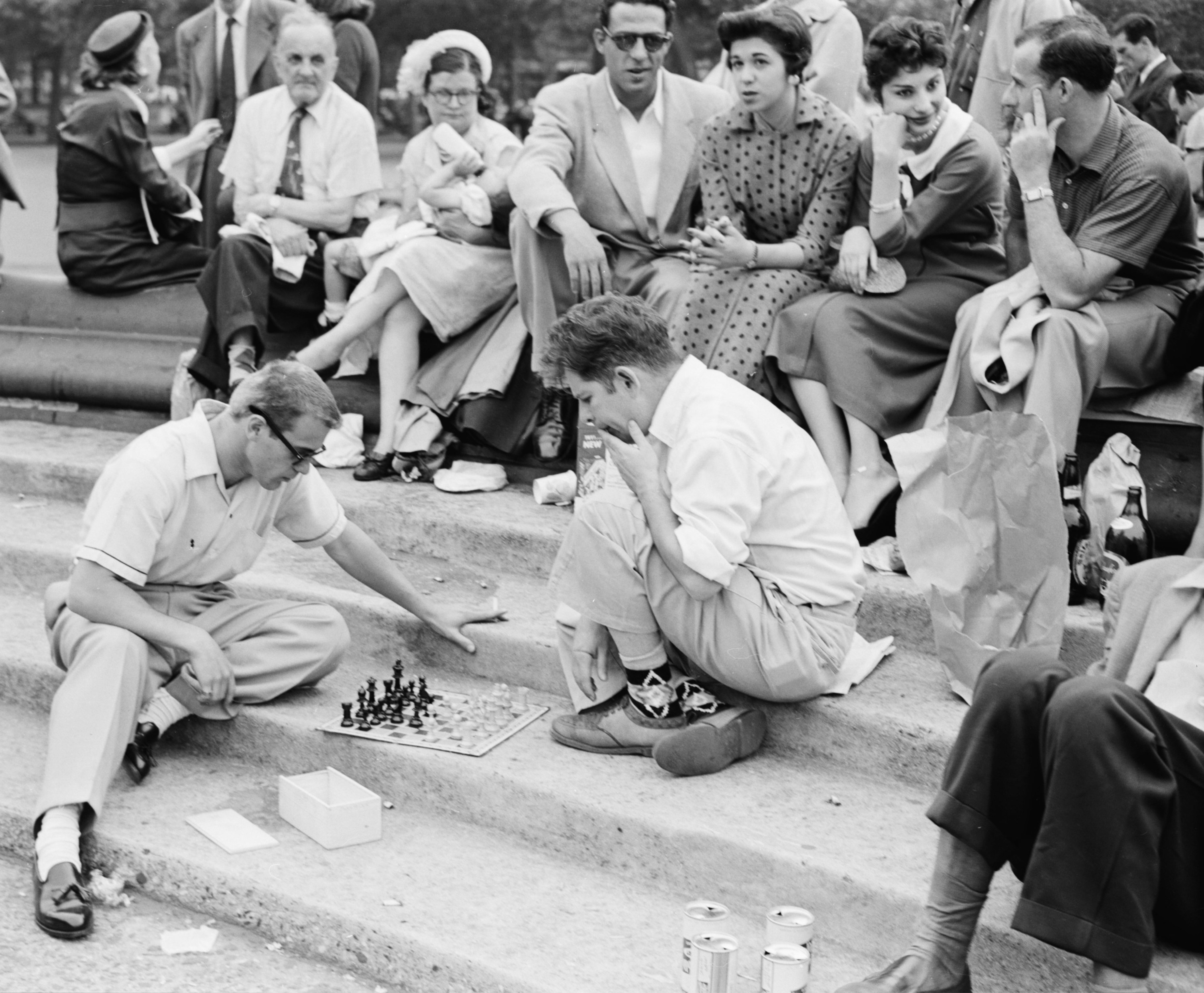 A group of people sitting on stairs at a park surround two men kneeling and playing chess