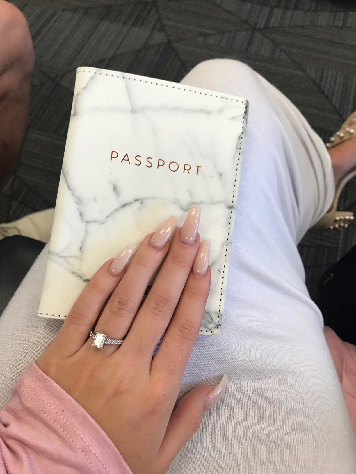 A reviewer holding the white marble passport holder in their lap
