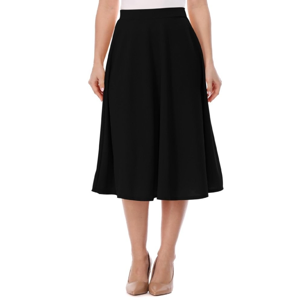 model wears black midi skirt and nude heels
