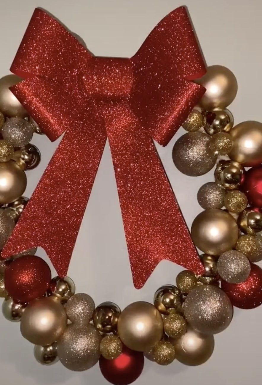A wreath made of sparkling red and gold ornaments