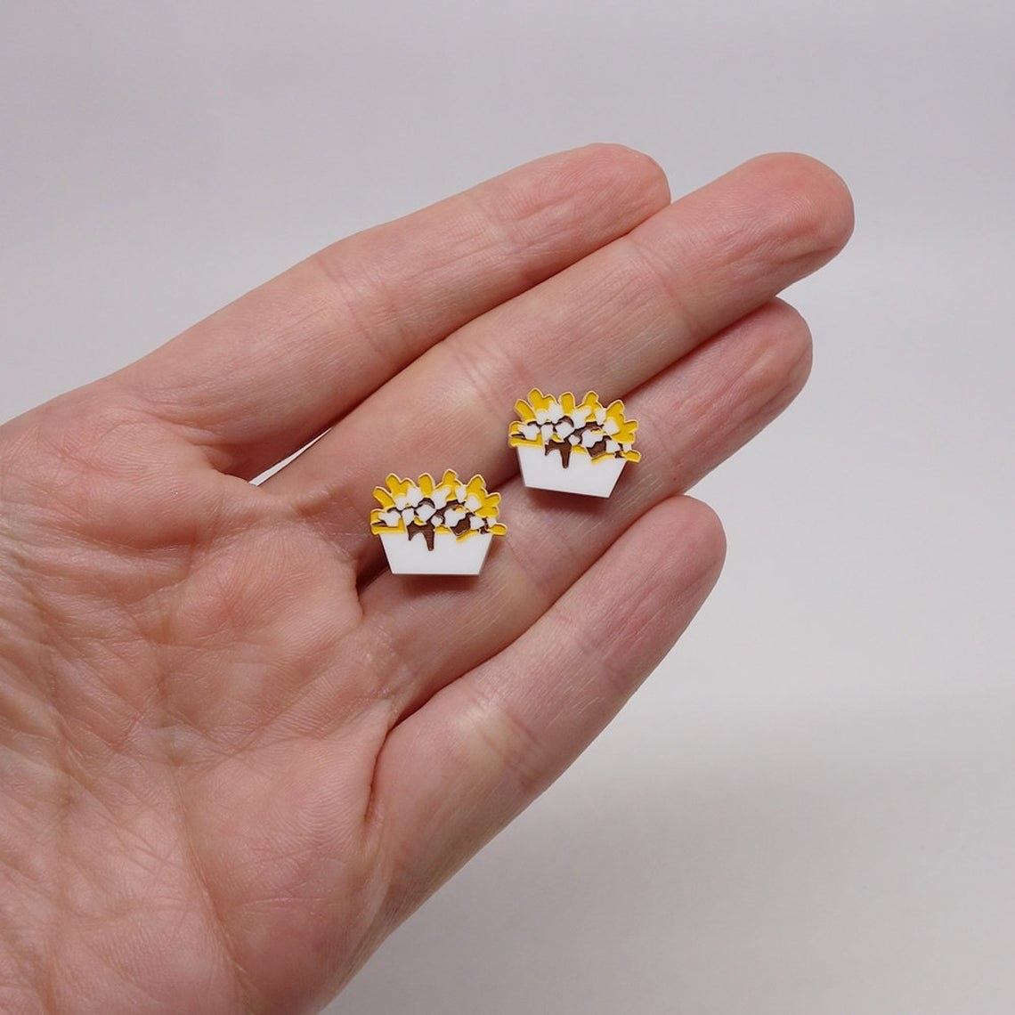 A person holding the poutine studs