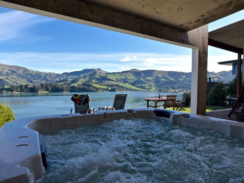 A hot tub looking out onto a bay with rolling hills in the background
