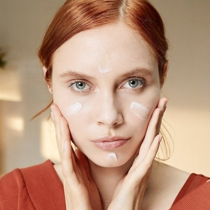 A person applying the gel moisturizer to their face