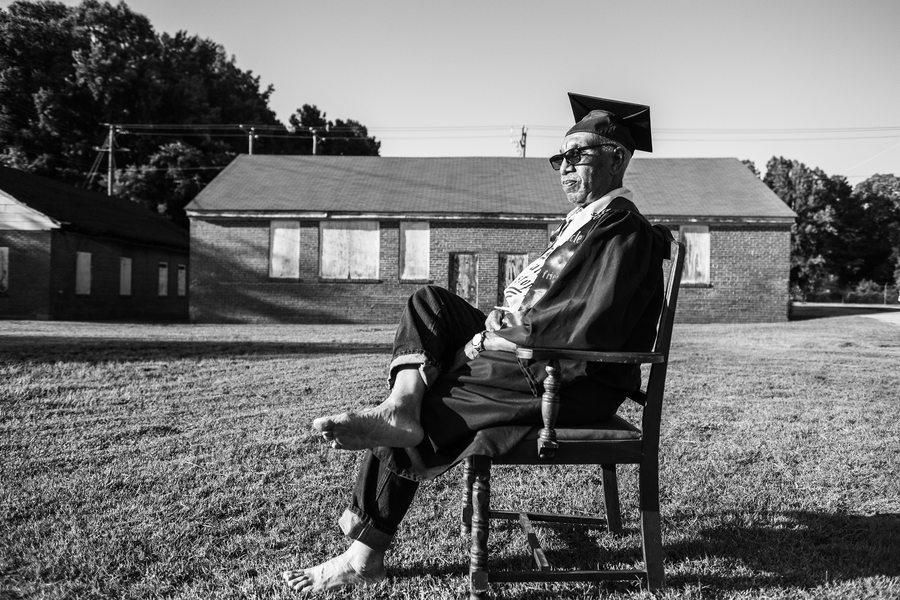 A Black man in graduation robes sits barefoot on a chair in a backyard