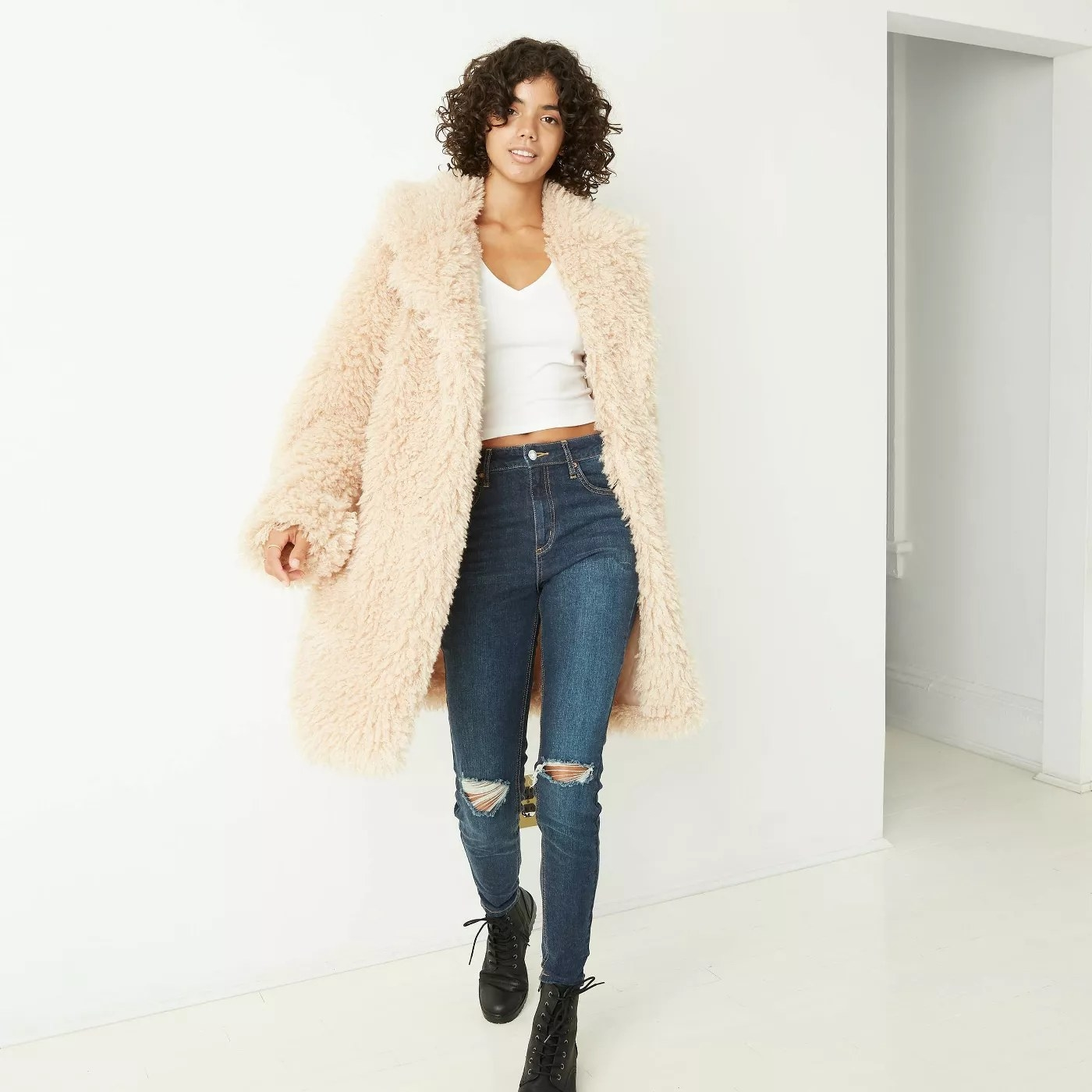 Light beige jacket that is knee length. Model is wearing jeans, white tank, and black combat boots.