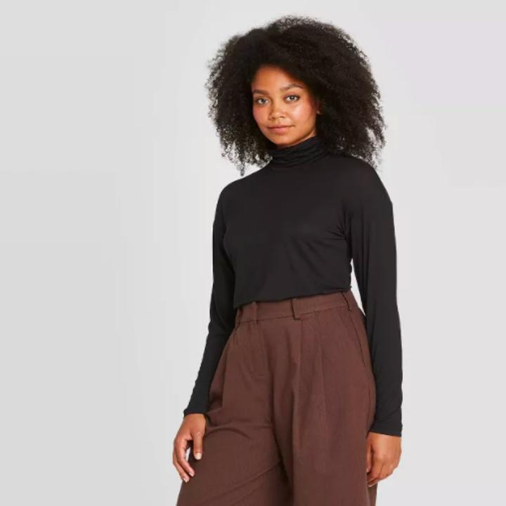 a model wearing the turtleneck in black