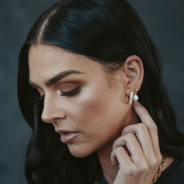 A model wearing one of the pearl beaded hoops and one of the small pearl and gold drop earrings