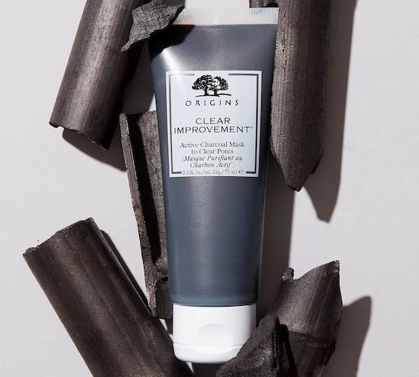 The tube of the charcoal mask surrounded by pieces of charcoal