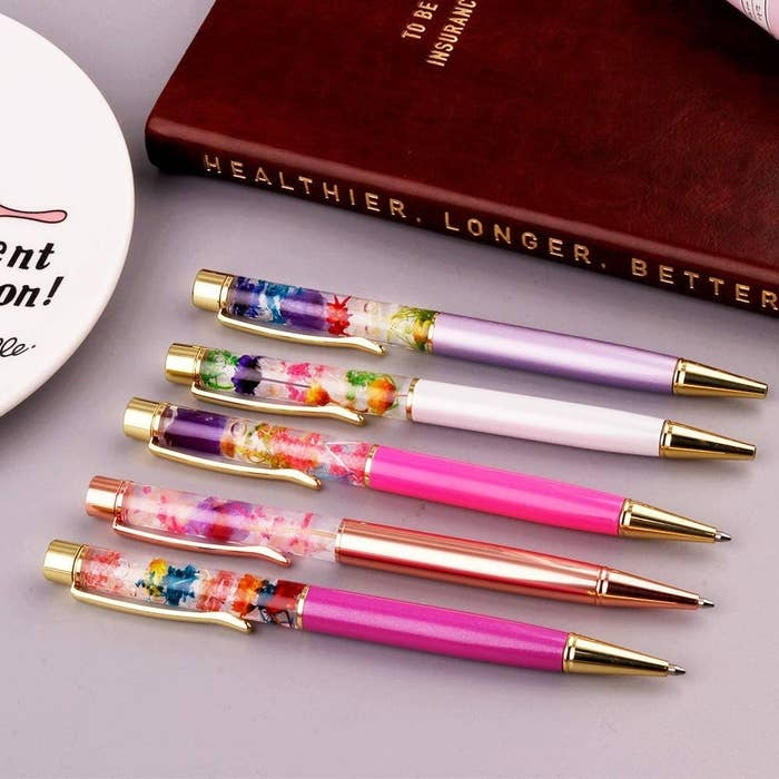 The five gold pens with clear tops filled with small flowers, each with a different color bottom half in shades of pink and purple