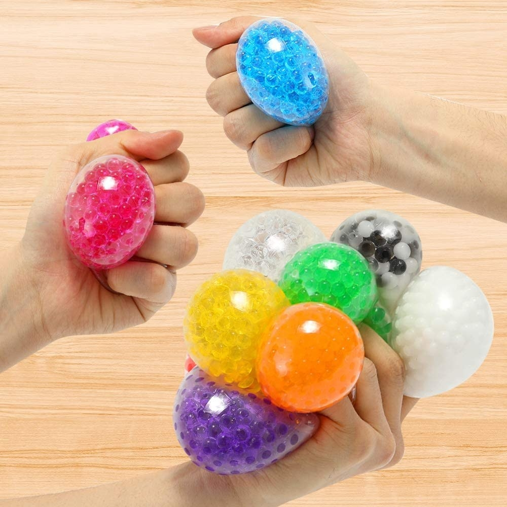 three hands squeezing water bead stress balls