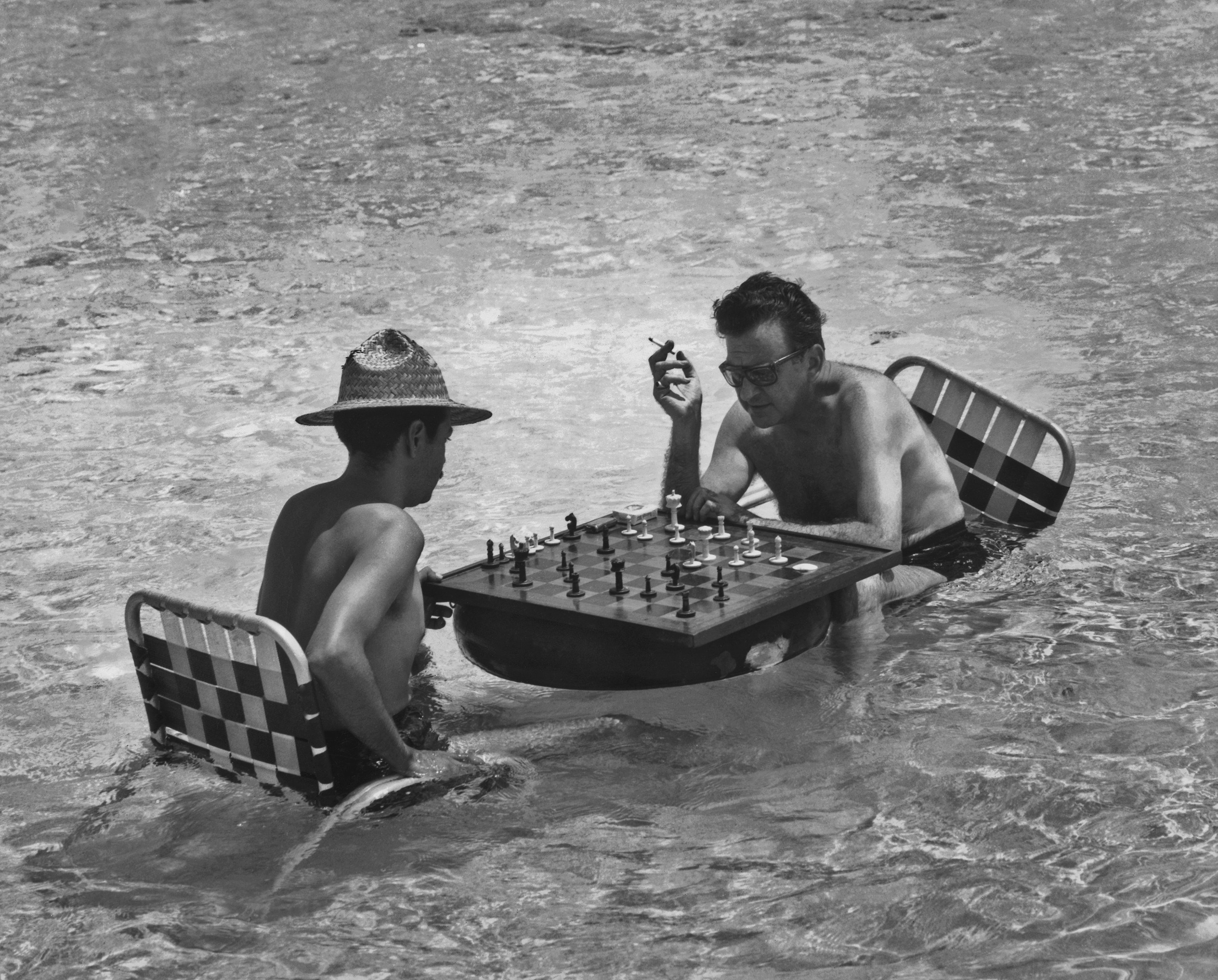 Two men sitting in the water in beach chairs play chess on a board that floats on an inner tube