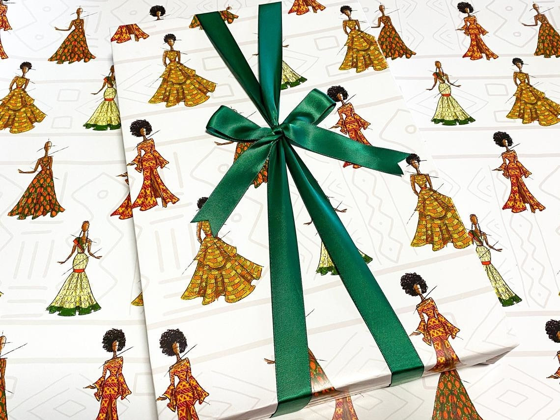 The white wrapping paper with hand-drawn models wearing Kwanzaa outfits