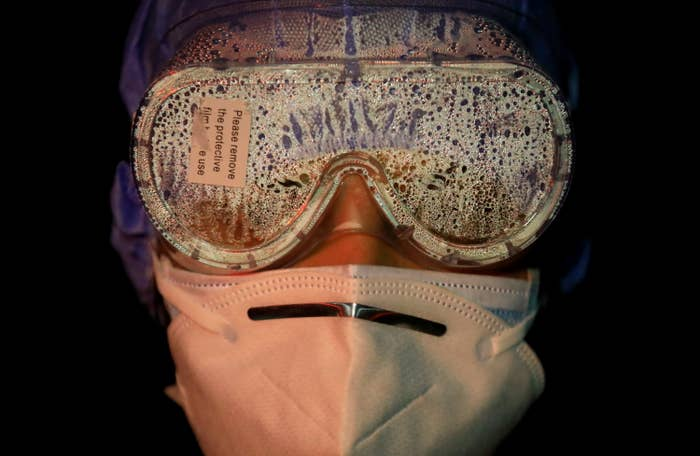 "The goggles of a woman wearing two face masks are coated in vapor; a sticker attached to their front reads ""Please remove the protective film before use"""