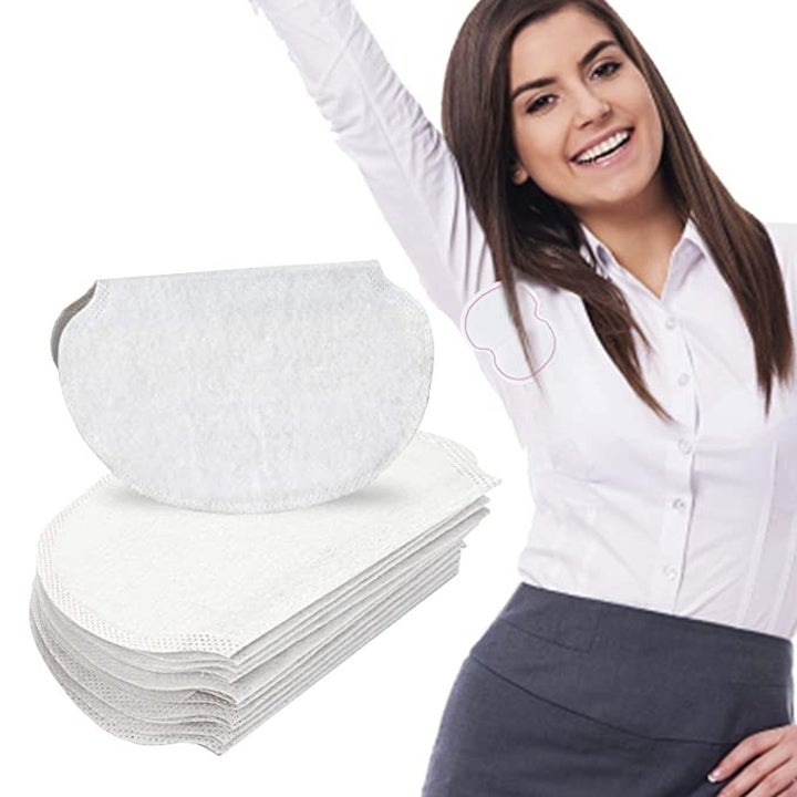 A model wearing a white shirt with an outline of where the sweat pad would be placed at the underarm inside the shirt, next to a stack of the underarm pads with one on top that is folded in half