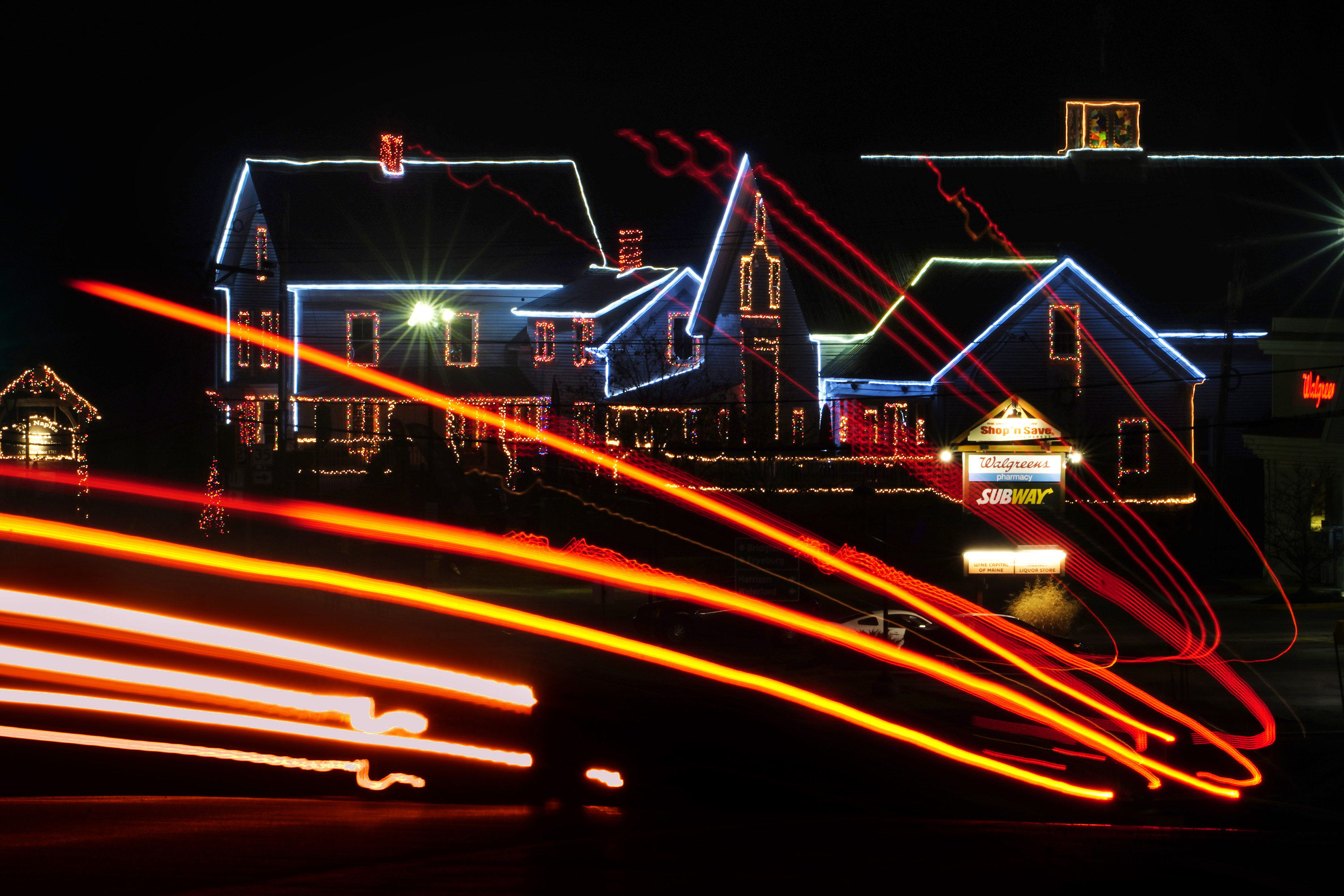 Bright lights in swooping colors, with a decorated house in the background.