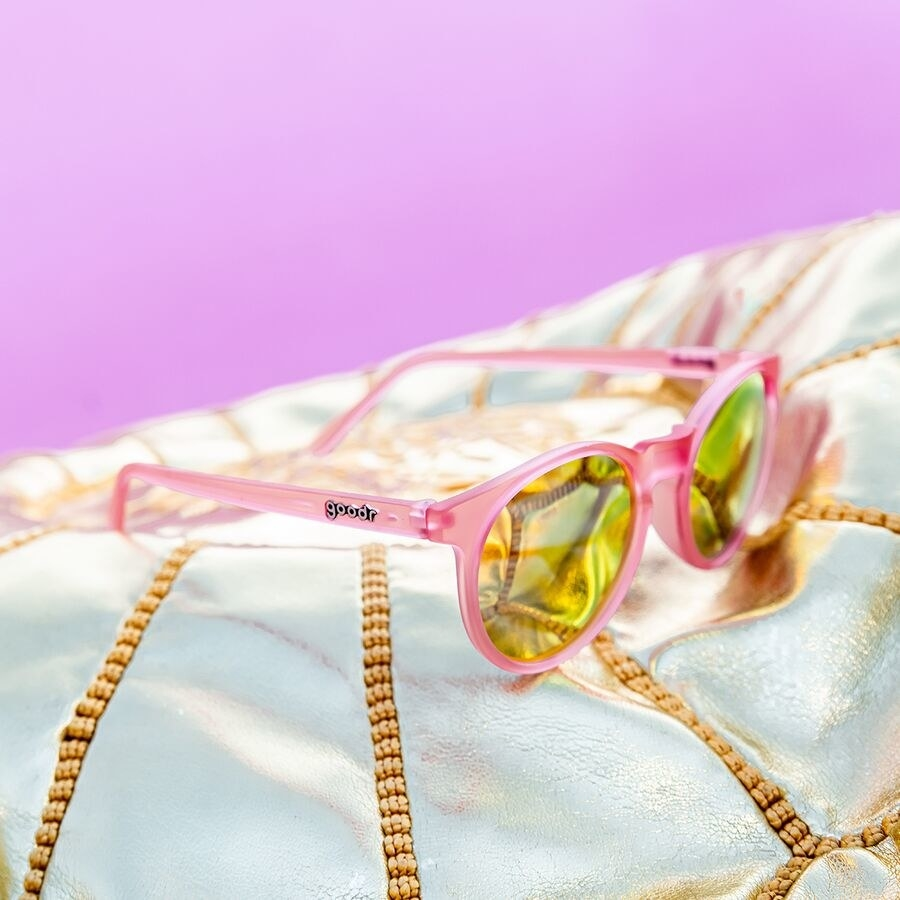Polarized pink sunglasses with yellow lenses on white cushion