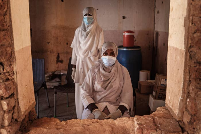 Two women in veils and protective equipment in a small room, seen through a window without glass