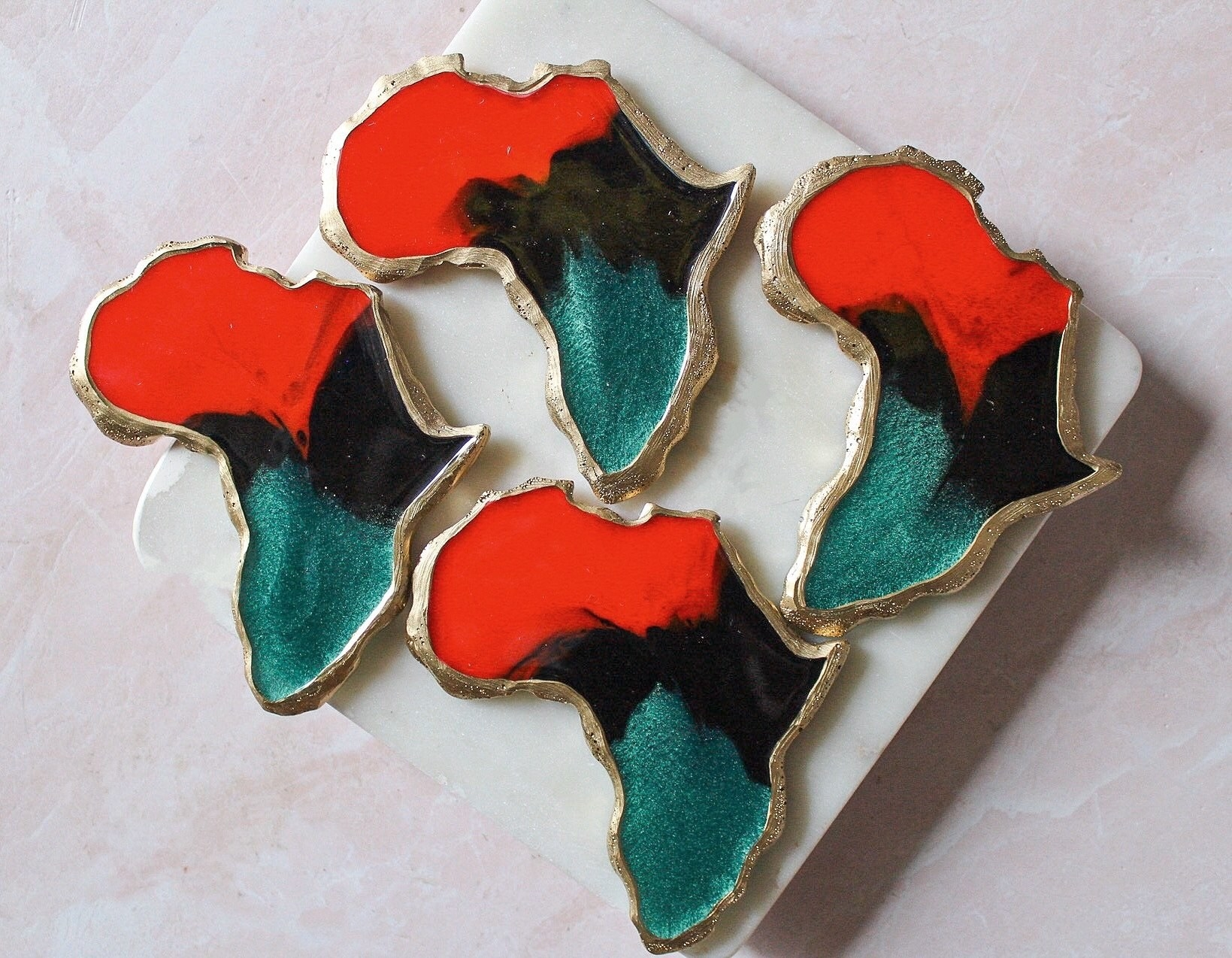 Four coasters red, black, and green coasters shaped like Africa