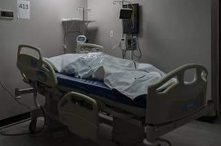 A deceased patient in a body bag on a bed in a COVID-19 intensive care unit.