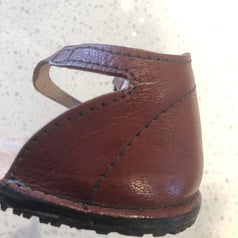 A reviewer photo of the same leather show with the previously-torn ankle strap repaired with Shoo Goo