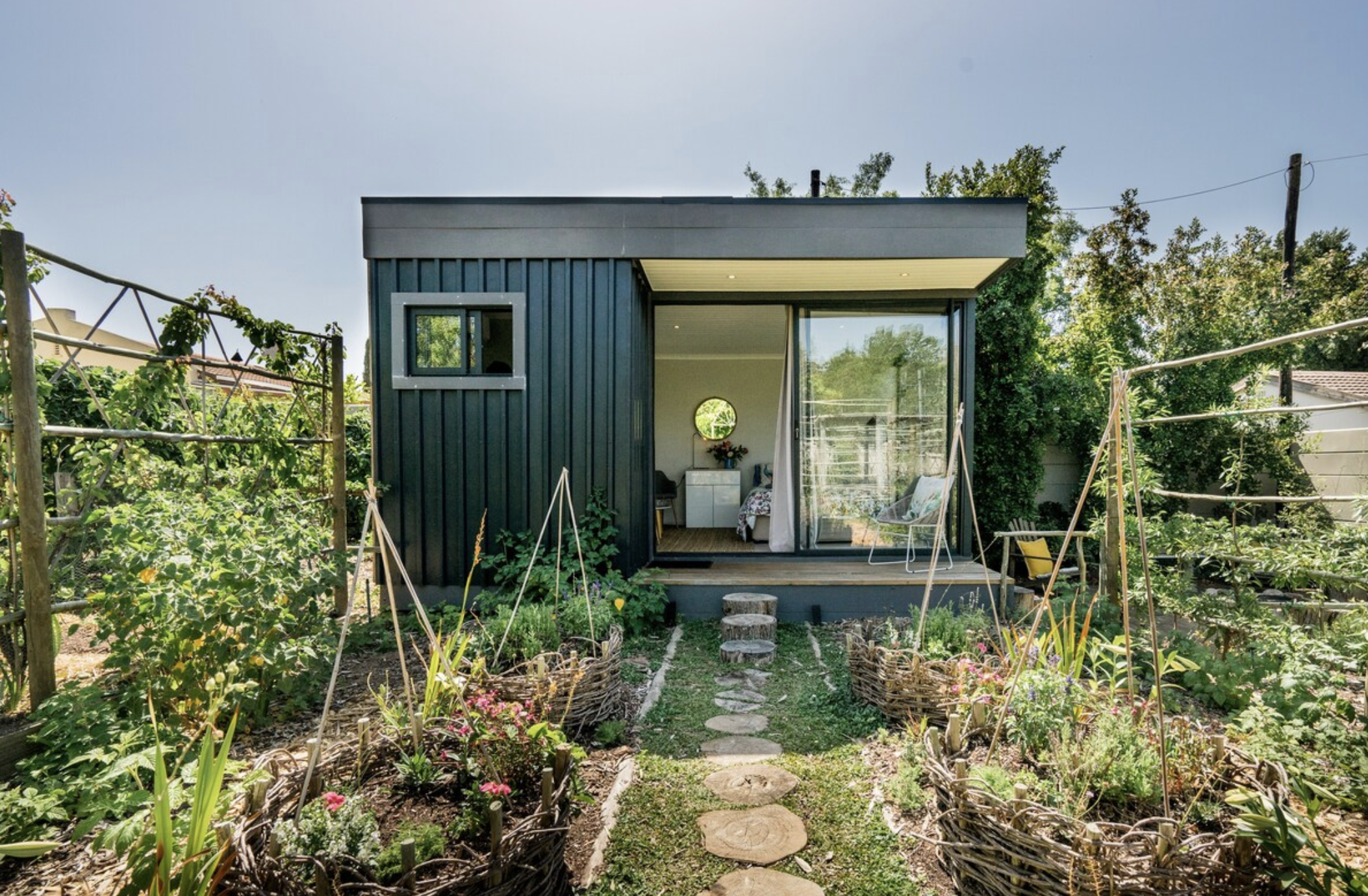 A rectangular metal house in the middle of a garden, accessible by cute stone path