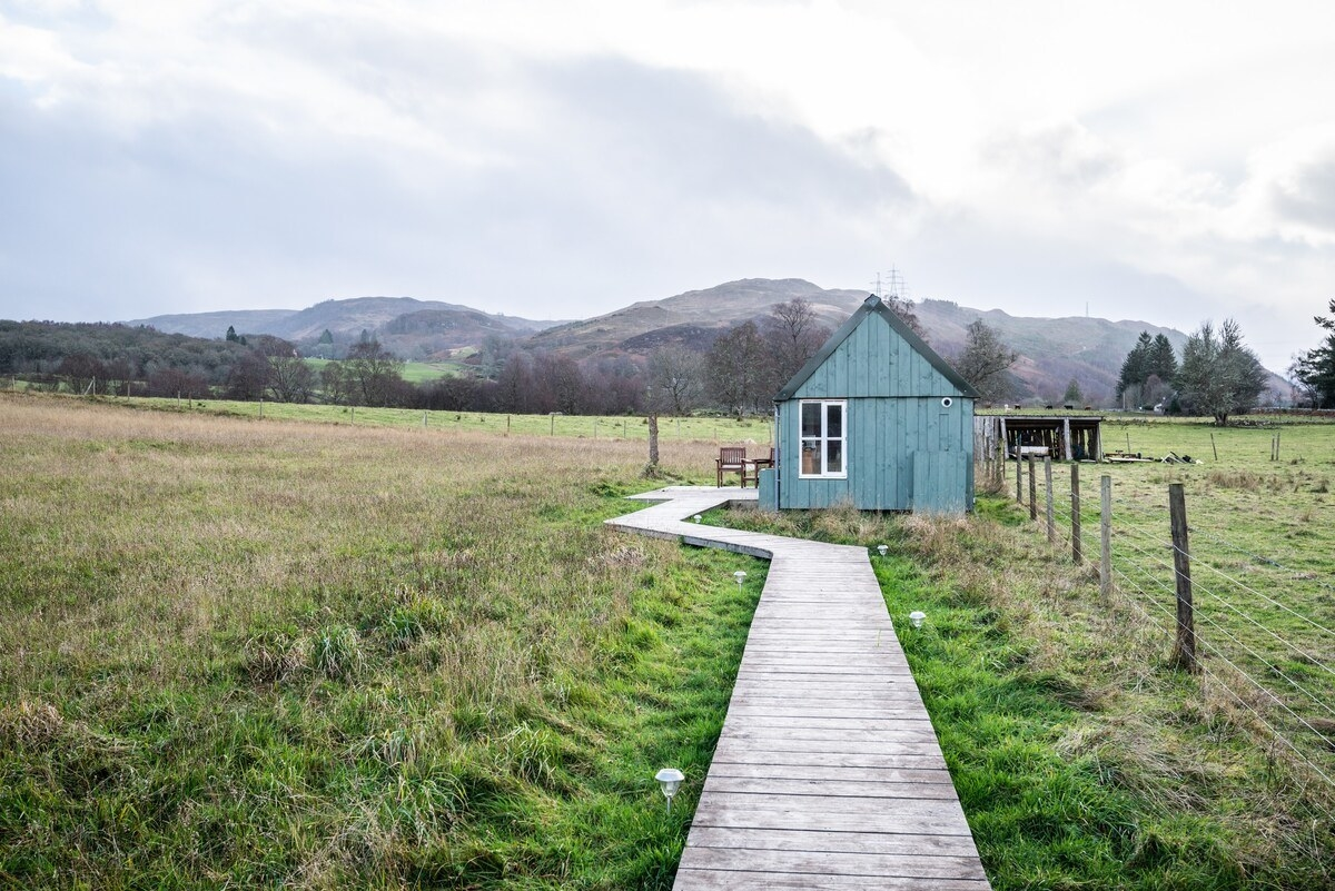 A wooden boardwalk leading across farmland to a small blue A-frame house