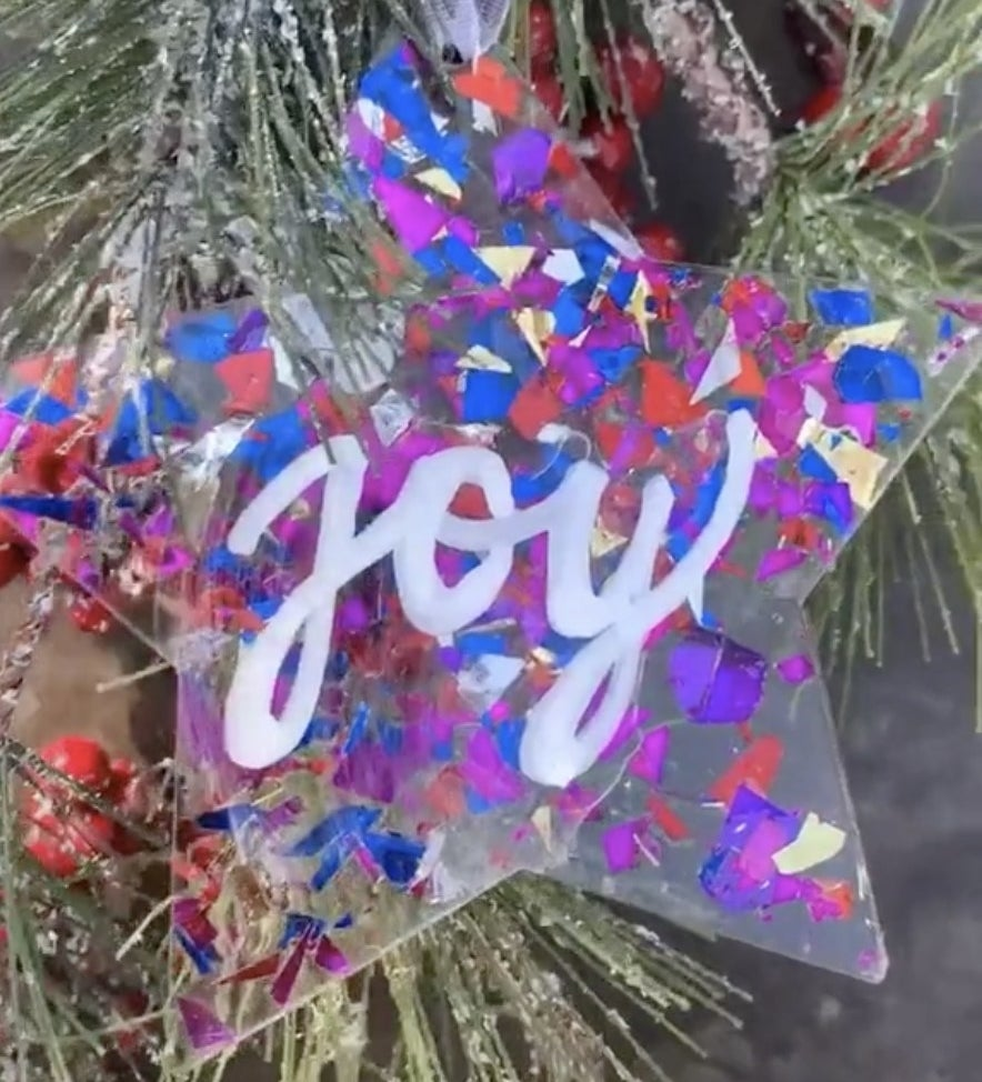 A star ornament covered in purple and blue confetti