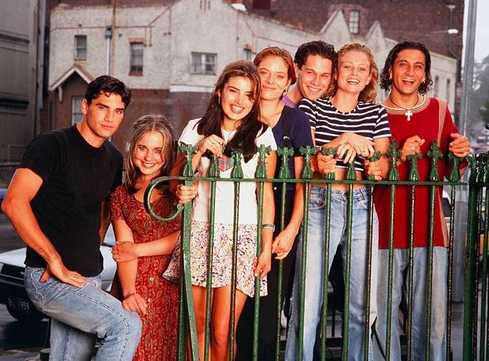 The cast of Heartbreak High pose for a promo photo standing behind a metal fence