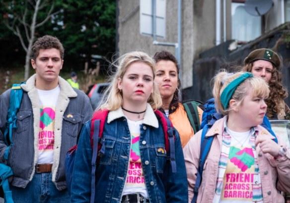 "The cast of Derry Girls wearing ""Friends Across the Barricade"" t-shirts"