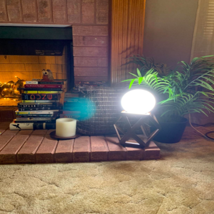 a reviewer's photo of the light on a wooden base in a living room