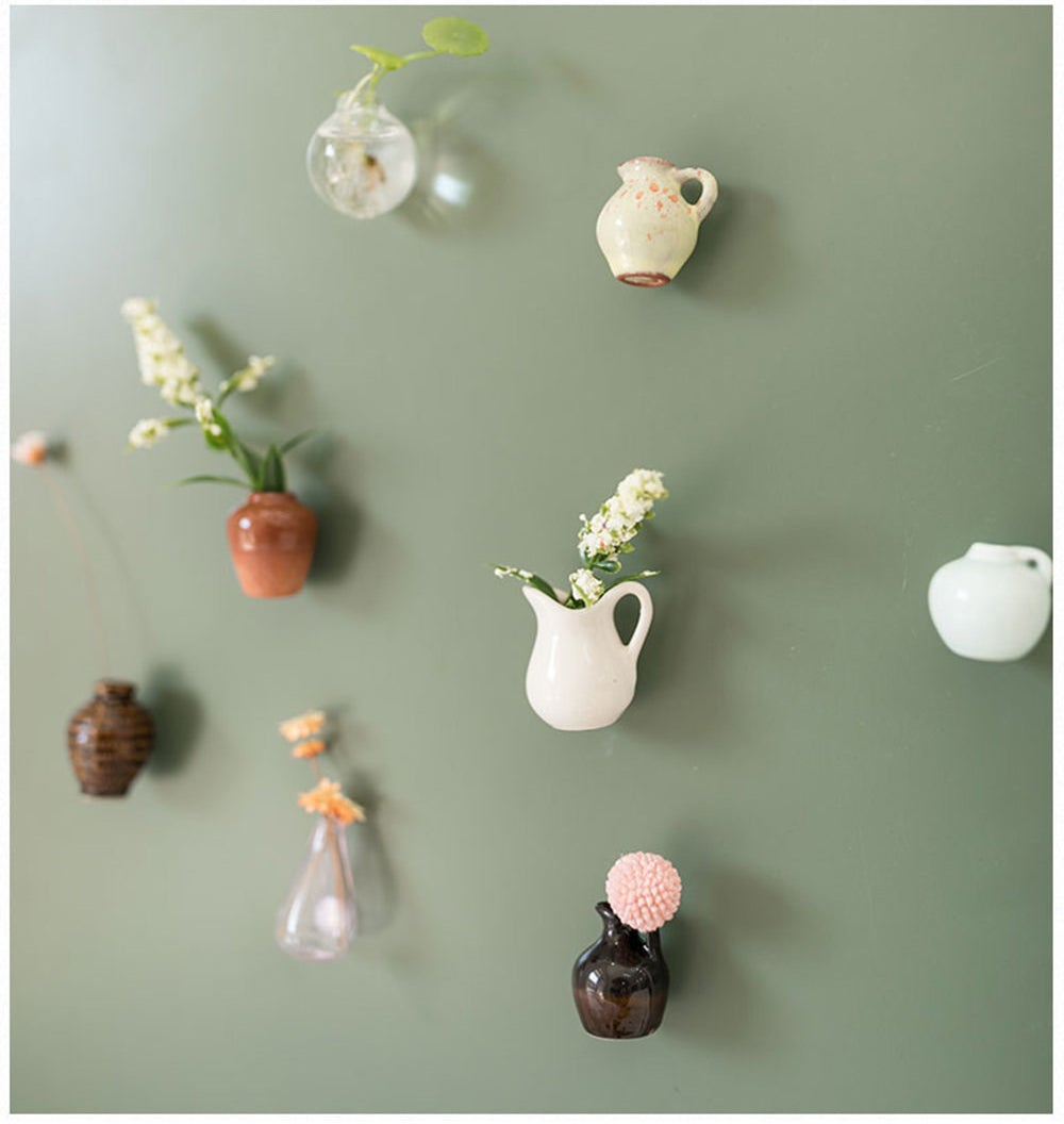 eight different tiny vases, some with plants inside of them