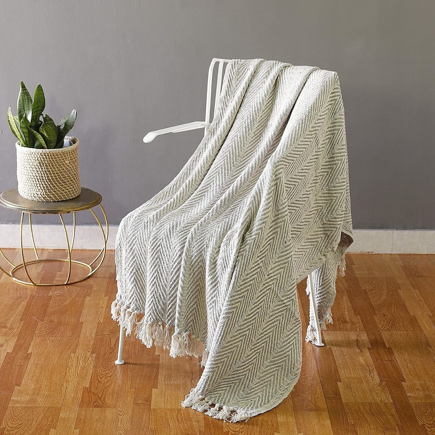 A white blanket with a tight chevron print in grey draped across a chair.