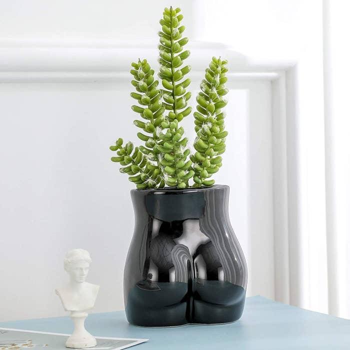 black flower vase shaped like a butt
