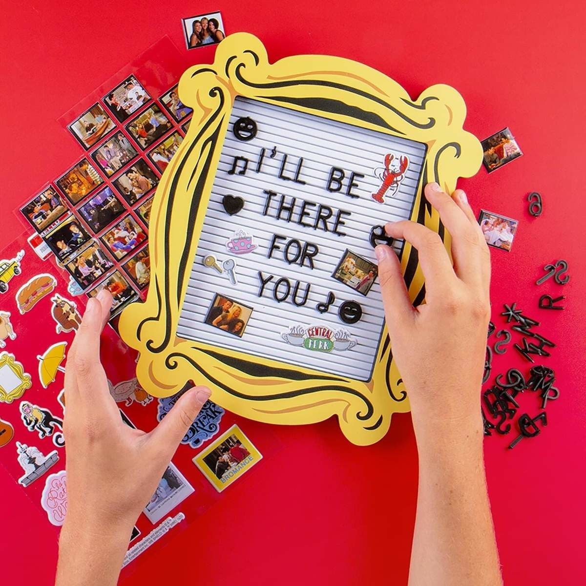 The letterboard shaped like the yellow frame from friends with I'll be there for you written on it with icons like the central perk logo and a lobster