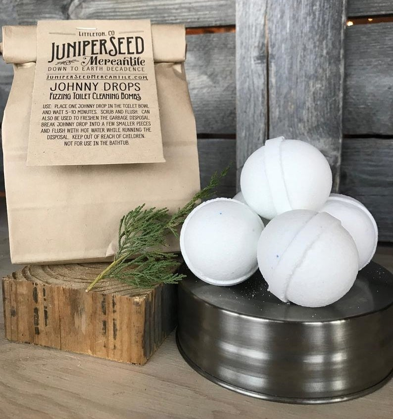 White bath bombs next to the brown paper bag packaging