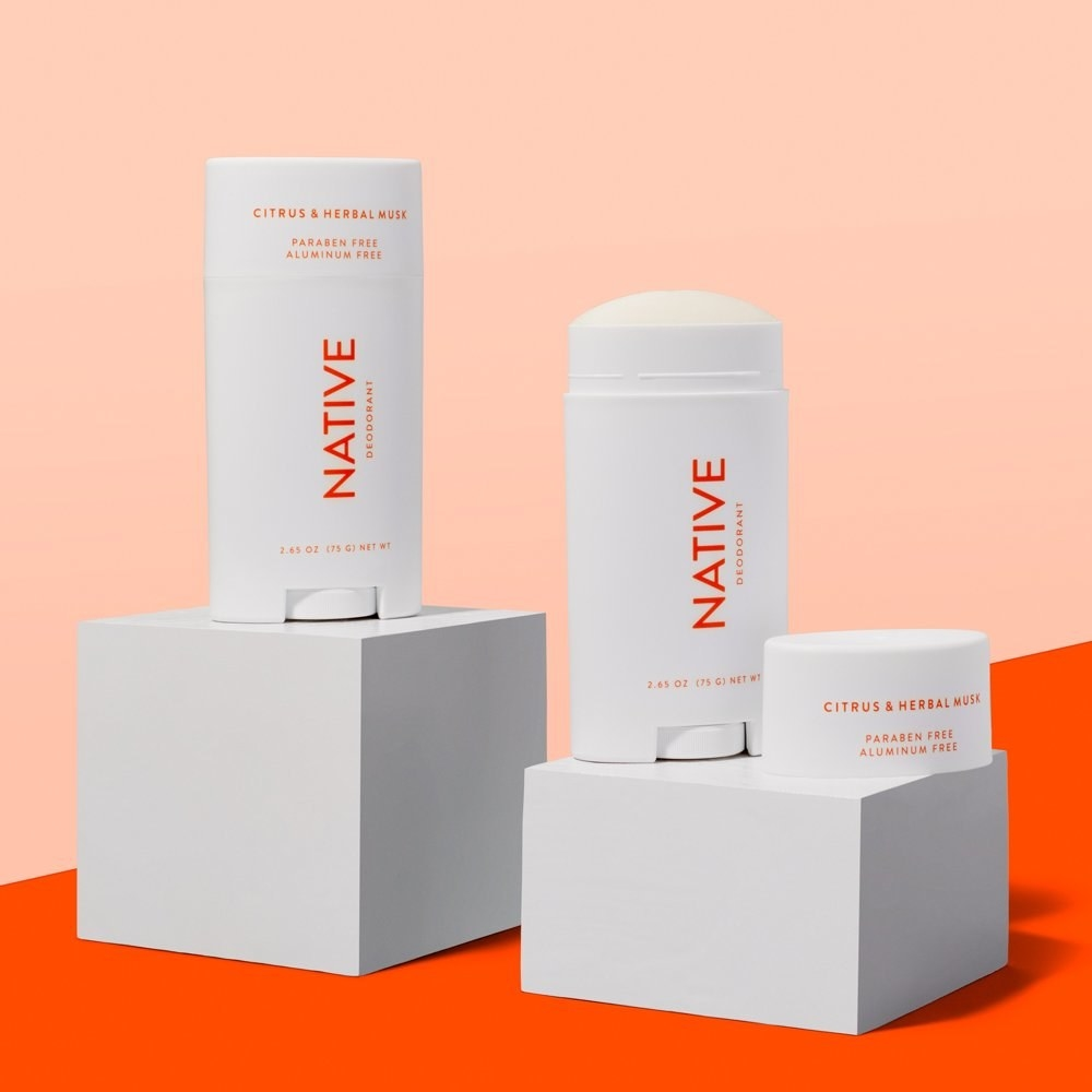 two white citrus and herbal musk deodorants on display boxes with a red and pink background
