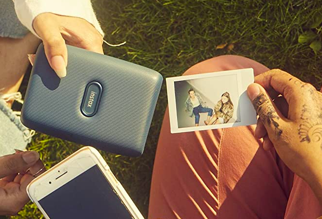 The Instax photo printer from Fujifilm beside a photo and a cell phone