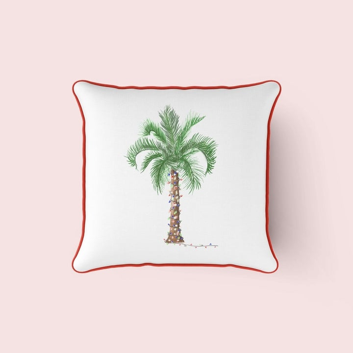 a white pillow with a palm tree on it covered in holiday lights and red trim