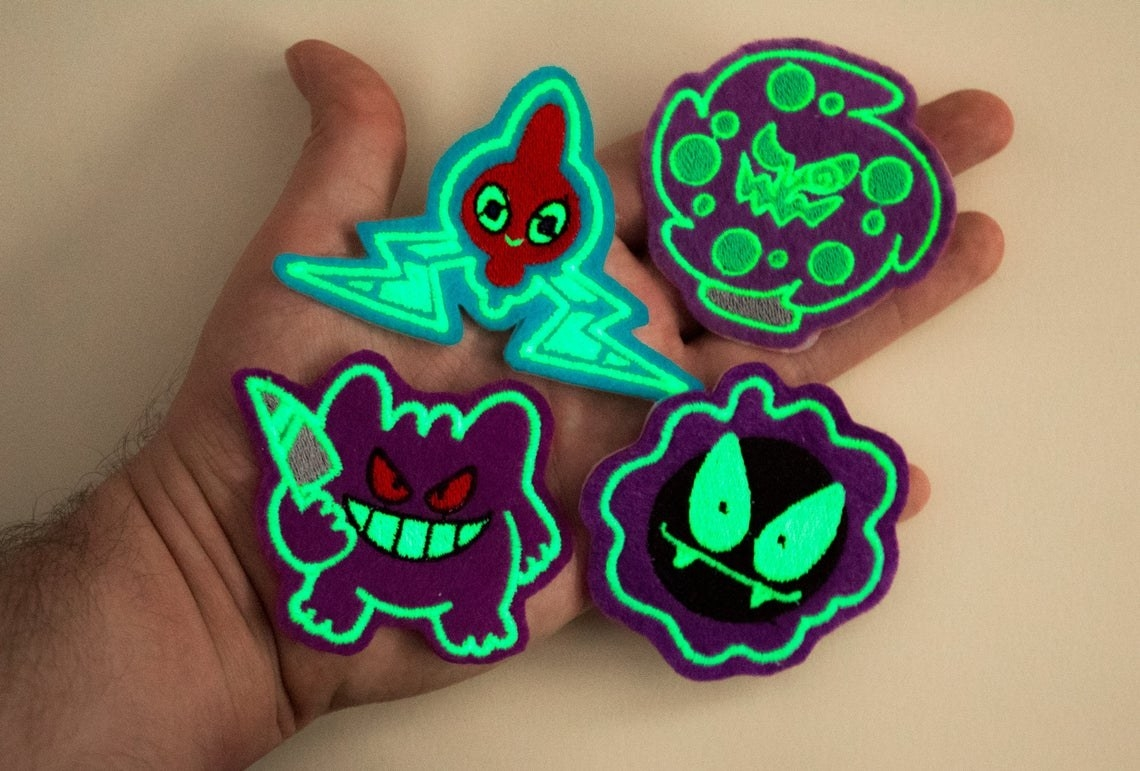 hand holds patches that look like ghastly, gengar, spiritomb, and rotom