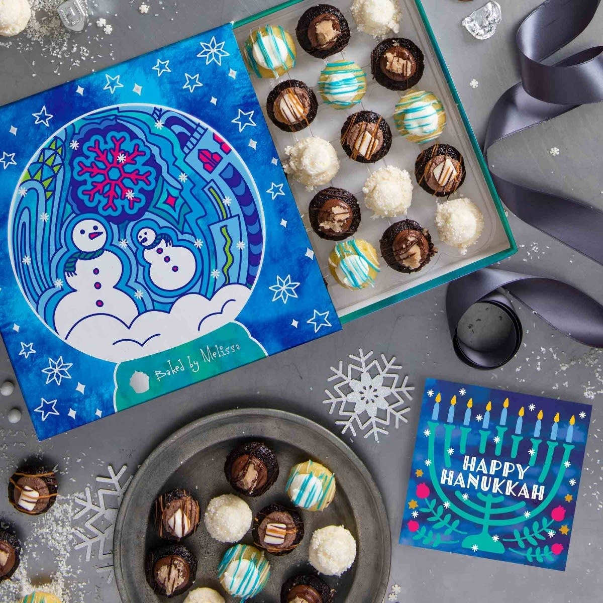 box with blue and pink snowman design with colorful mini cupcakes inside and a card with a menorah that says happy hanukkah