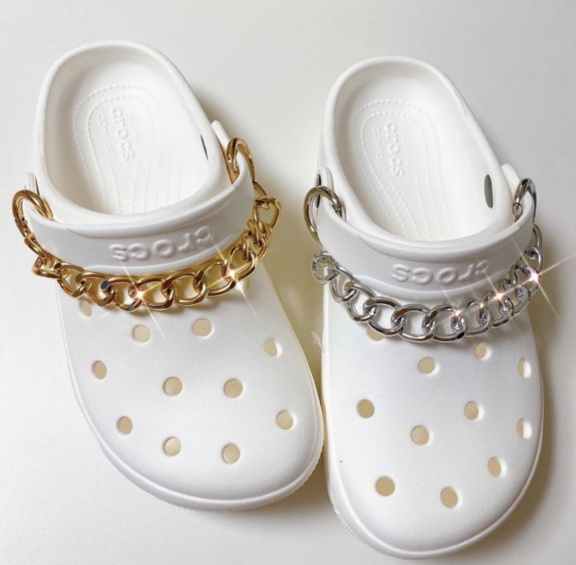 a pair of white crocs with chunky chains around the tops